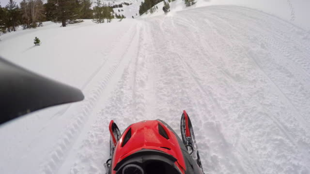 pov of a man snowmobiling in the mountains. - wintersport stock-videos und b-roll-filmmaterial