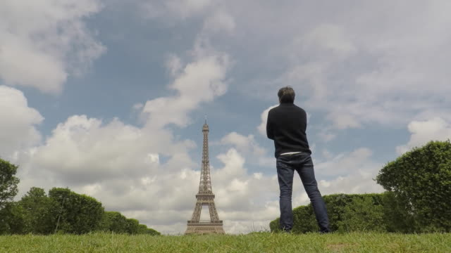 a man standing in front of the Eiffel Tower