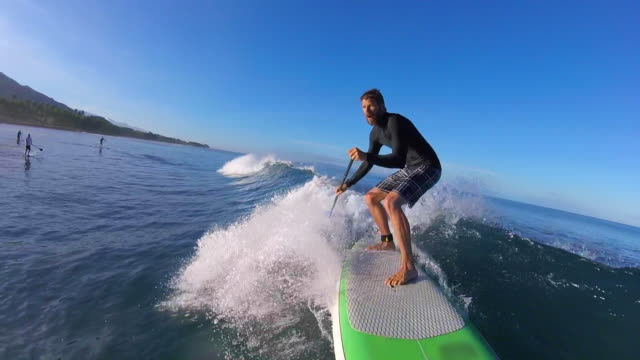 pov of a man sup stand-up paddleboard surfing. - slow motion - wassersport stock-videos und b-roll-filmmaterial