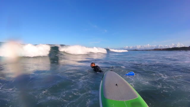 POV of a man sup stand-up paddleboard surfing. - Slow Motion