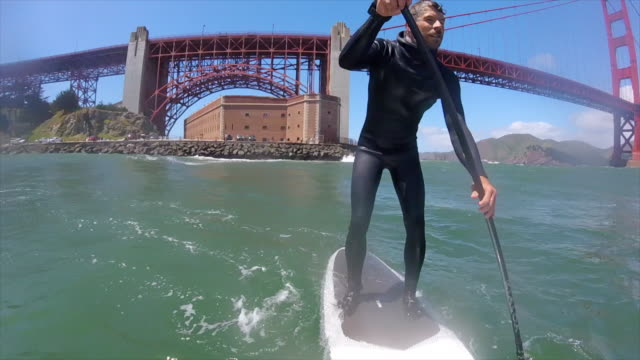 POV of a man sup stand-up paddleboard surfing under the Golden Gate Bridge.