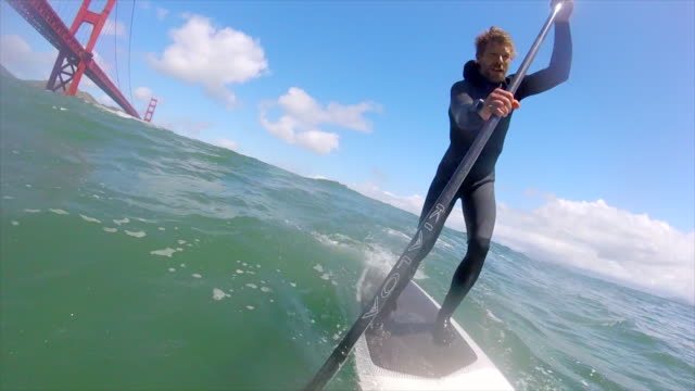 pov of a man sup stand-up paddleboard surfing under the golden gate bridge. - slow motion - pagaiare video stock e b–roll