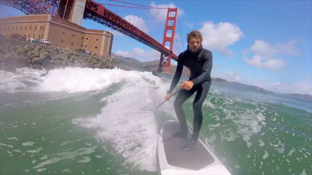 POV of a man sup stand-up paddleboard surfing under the Golden Gate Bridge. - Slow Motion