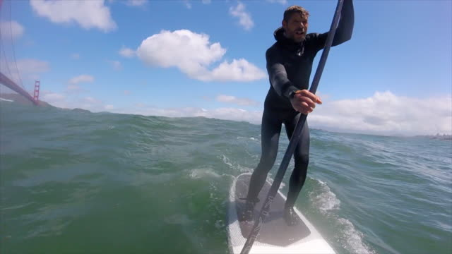 pov of a man sup stand-up paddleboard surfing under the golden gate bridge. - slow motion - digital camcorder stock videos & royalty-free footage