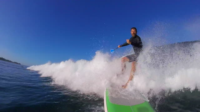 POV of a man sup stand-up paddleboard surfing.