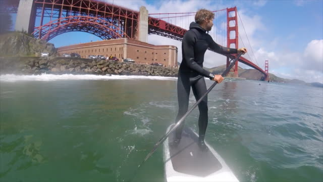 POV of a man sup stand-up paddleboarding under the Golden Gate Bridge. - Slow Motion