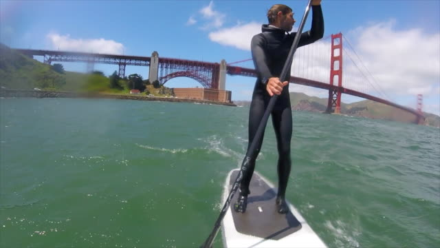 POV of a man sup stand-up paddleboarding under the Golden Gate Bridge.