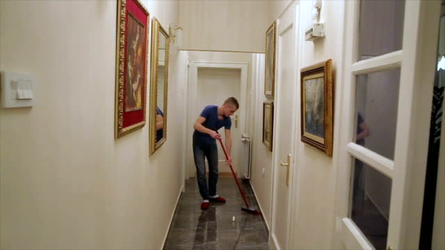 a man sweeping the floor with broomstick at home - husband stock videos & royalty-free footage