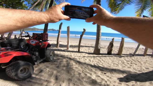 POV of a man taking a picture with his mobile device near his ATV quad motorized vehicle and a scenic beach.