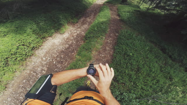 pov of a man trail running and checking sportwatch and mobile phone - wearable computer stock videos & royalty-free footage