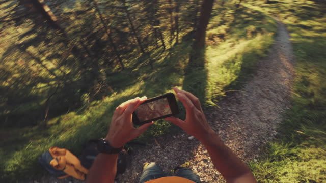 POV of a Man trail running and checking sportwatch and mobile phone