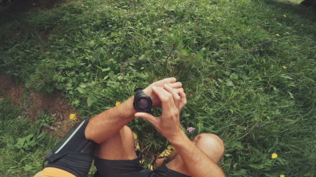 pov of a man trail running and checking sportwatch and mobile phone - sportswear stock videos & royalty-free footage