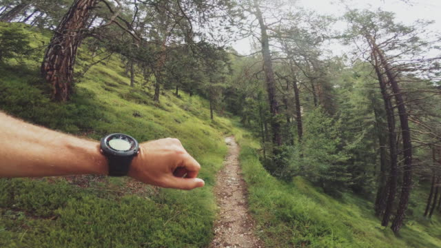 pov of a man trail running and checking sportwatch - point of view video stock e b–roll