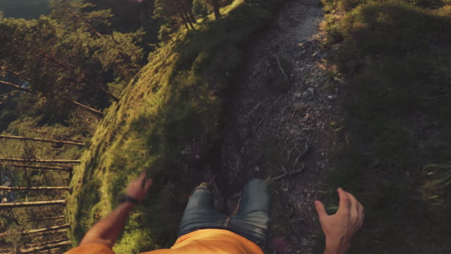pov of a man trail running offroad in a mountain forest - strada in terra battuta video stock e b–roll