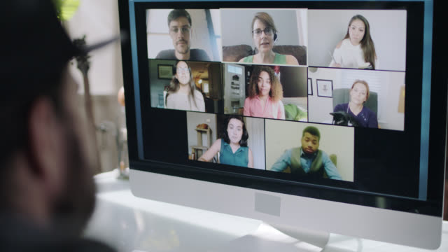 stockvideo's en b-roll-footage met cu of a man video conferencing with his coworkers. - videogesprek