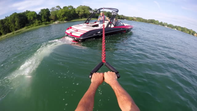 POV of a man wakeboarding behind a boat.