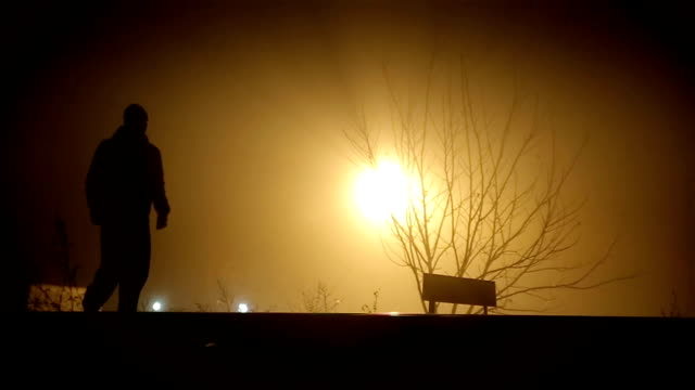 a man walks on a foggy night - loneliness stock videos and b-roll footage