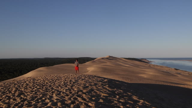 a man walks on summit of the pyla dune, a summer morning - arcachon stock videos & royalty-free footage