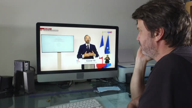a man watches on his computer the press conference of the french prime minister edouard philippe during france's coronavirus lockdown - headshot stock videos & royalty-free footage