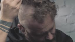 a man with a beard shaves his head with an electric trimmer. bearded punk hipster shaves his mohawk. 4k video. slow motion. 23.98 fps