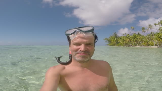a man with mask and snorkel standing in the sea - french overseas territory stock videos & royalty-free footage
