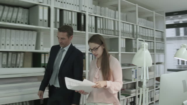 a manager and office employee having an exchange in a creative, stylish office