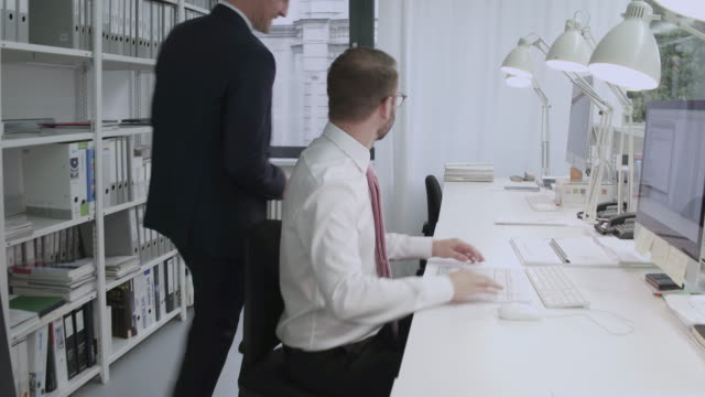 vídeos de stock e filmes b-roll de a manager and office employee having an exchange in a creative, stylish office - camisa e gravata