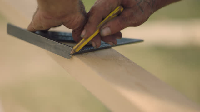 cu of a mature construction worker's hands measuring and marking a line to cut wood - semi dress stock videos & royalty-free footage