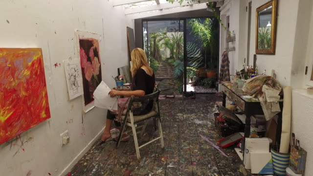a mature woman painting in her art studio at home. - apron stock videos & royalty-free footage