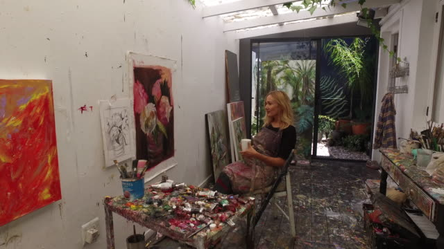 a mature woman painting in her art studio at home. - art studio stock videos & royalty-free footage