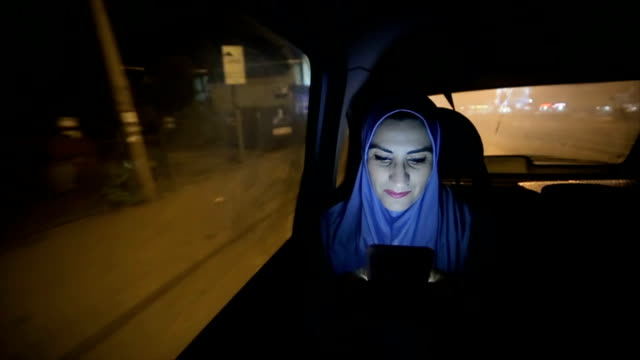 a modern arab woman rides in a car  at night - saudi arabia stock videos & royalty-free footage