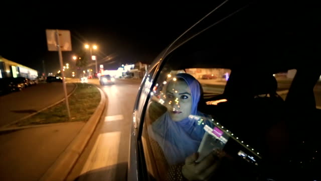 a modern arab woman rides in a taxi at night - saudi arabia stock videos & royalty-free footage