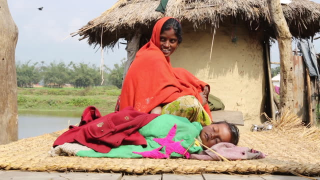 ws of a mother in a red sari who is sitting behind her sleeping child in front of a mud hut in a village near birgunj a border town in parsa district... - indian mom stock videos & royalty-free footage