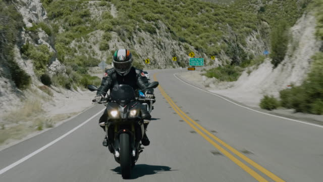 a motorcyclist leads two other riders on a high-speed ride on a mountain highway - biker jacket stock videos and b-roll footage