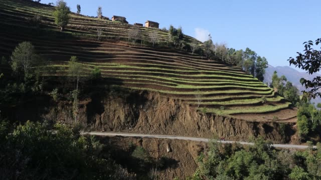 WS PAN of a motorcyclist that is driving down a narrow road in the mountains near Kathmandu Nepal Several isolated houses can be seen in the...