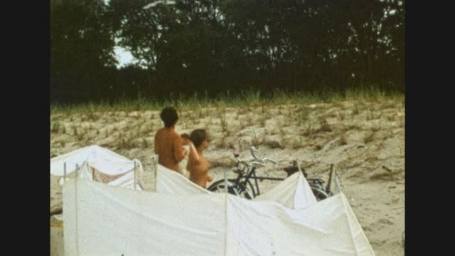 a naked young man and a naked young woman feeding sea gulls by throwing peaces of bread at them at the beach of the baltic sea / nudist / shot in... - fkk stock-videos und b-roll-filmmaterial