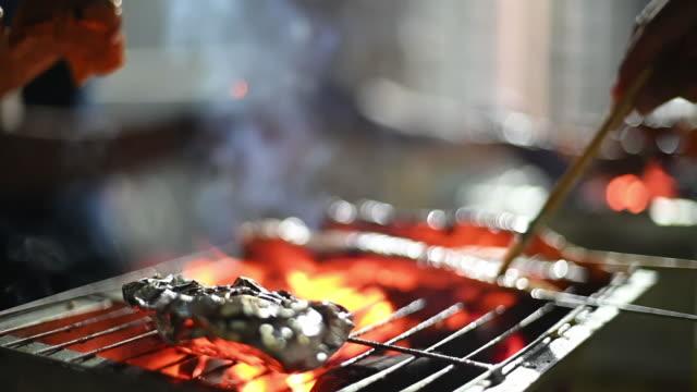 vídeos y material grabado en eventos de stock de una fiesta de barbacoa de la noche reunión con preparación de alimentos con ala de pollo - hoja de aluminio