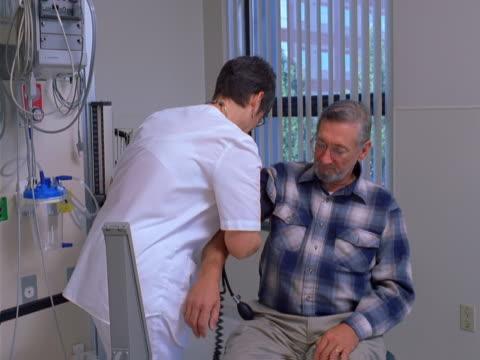 a nurse takes a man's blood pressure reading - artbeats bildbanksvideor och videomaterial från bakom kulisserna