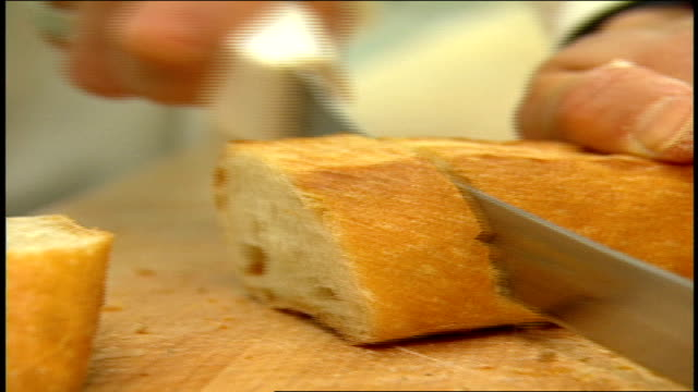 CU a Person Slicing Bread with a Serated Knife