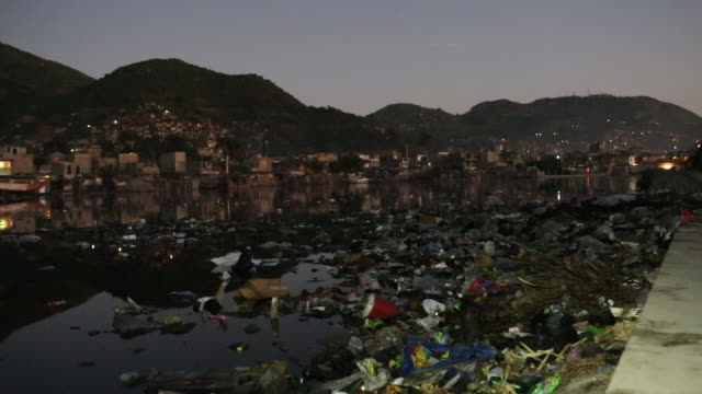 ws of a polluted lake that is being used for washing with different sorts of plastic waste that is floating on the water in caphaïtien a commune on... - plastic cap stock videos & royalty-free footage