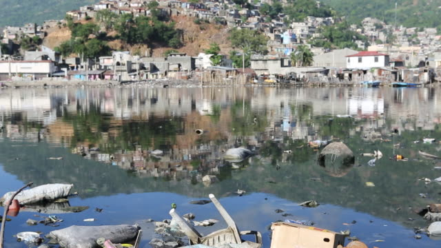 tu of a polluted lake with different sorts of plastic waste that is floating on it in caphaïtien a commune on the north coast of haiti and capital of... - plastic cap stock videos & royalty-free footage