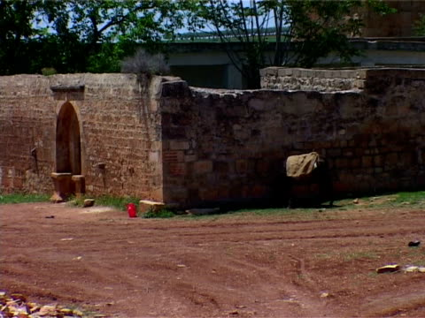 of a red brick/stone wall with an arched entrance surrounding a shrine or folly located on the outskirts of the archaeological site of cyrrhus . - surrounding wall stock-videos und b-roll-filmmaterial