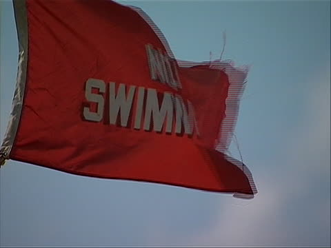 cu of a red flag stating the words no swimming is seen at a beach in point pleasant new jersey point pleasant beach has both public access and... - ocean avenue stock videos & royalty-free footage