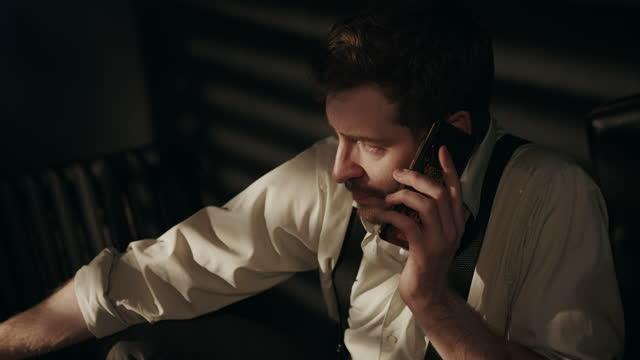 ein trauriger betrunkener unternehmer in hemd und zahnspange sitzt in einem dunklen raum, raucht zigarette und telefoniert und spricht über die probleme, die ihm passiert sind - one mid adult man only stock-videos und b-roll-filmmaterial