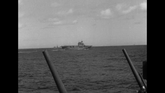 vs a seaplane flies alongside with numerous ships below / aircraft carriers seen from between gun barrels / vs high angle views of deck of ship with... - kriegsschiff stock-videos und b-roll-filmmaterial