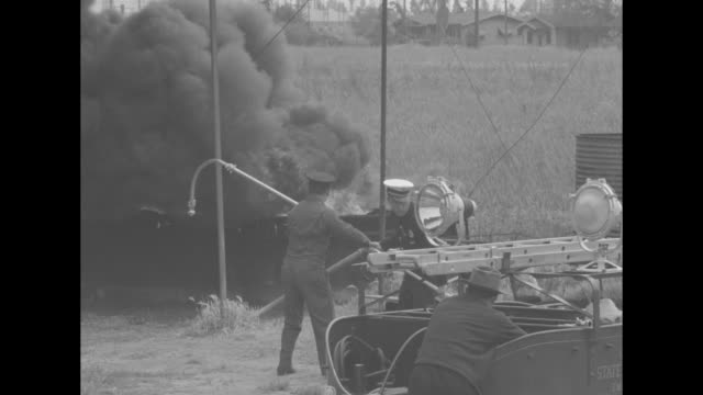 vs a sedan pulls a customized trailer to a stop in an industrial area and a man pours water onto a intense fire with spigots and a hose he approaches... - fire hose stock videos and b-roll footage