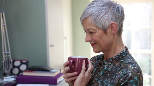 CU of a senior woman working on laptop and drinking a cup of tea.