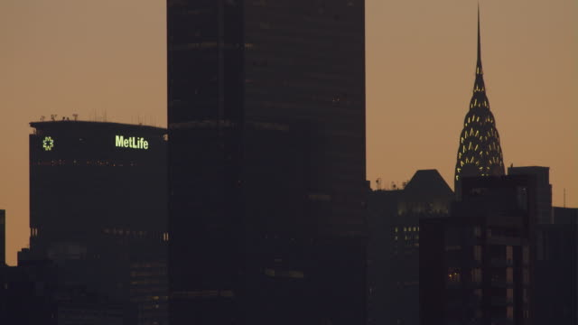 stockvideo's en b-roll-footage met cu of a series of buildings midtown, 1 penn plaza, the chrysler building, and the met life building early morning in silhouette - metlife building