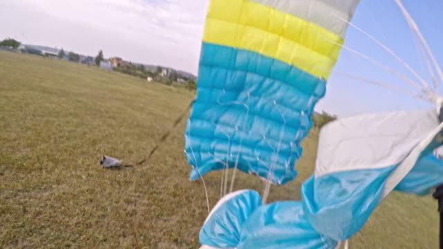 POV of a skydiver landing on a field