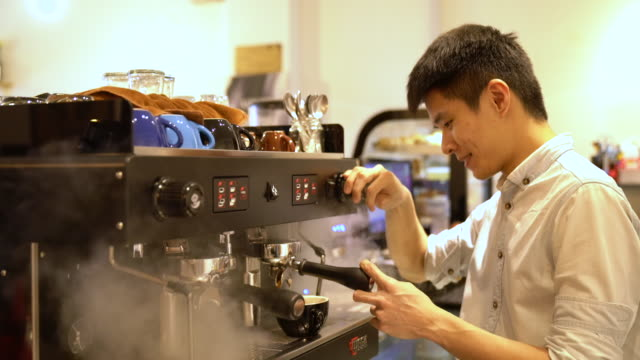 a small business owner barista preparing coffee for his customer in the cafe - malaysia stock videos & royalty-free footage